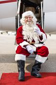 Full length portrait of happy Santa Claus holding milk glass while sitting on private jet's ladder