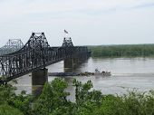 stock photo of barge  - Tugboat pushing barges beneath a bridge crossing the Mississippi River at Vicksburg - JPG
