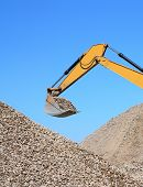 foto of dredge  - Rubble spilling out of the bucket dredge on background of blue sky - JPG