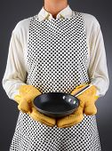 Closeup of a homemaker in an apron and oven mitts holding a pan. Vertical format over a light to dar