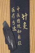 Acupuncture needles and mandarin calligraphy script. Translation describes acupuncture chinese medic