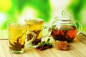 Cup and teapot of green tea with honey on table on bright background