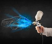 picture of gun shop  - Worker with airbrush gun painting hand drawn white car lines - JPG