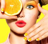 Beauty Model Girl takes Juicy Oranges. Beautiful Joyful teen girl with freckles, funny hairstyle, ye