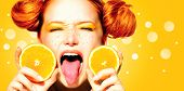 Beauty Model Girl with Juicy Oranges. Beautiful Joyful teen girl with freckles, funny red hairstyle and yellow makeup. Open mouth. Professional make up. Orange  Slices