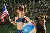 stock photo of biracial  - Preschooler holding US flag and beachball posing with dog - JPG