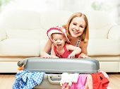 Mother And Baby Girl With Suitcase And Clothes Ready For Traveling On Vacation