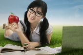 pic of indian apple  - Female student holding a red apple while studying at the park - JPG