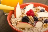 Bowl of delicious steel cut oats with fresh fruit, honey and orange juice
