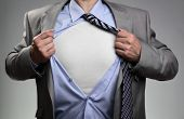 Businessman in classic superman pose tearing his shirt open to reveal t shirt with blank chest for m