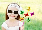 Smiling Little Girl In Sunglasses Playing With Windmill Toy