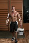 Bodybuilder Posing With Supplements For Copy Space