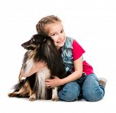 cute little girl is with her dog Sheltie isolated on white