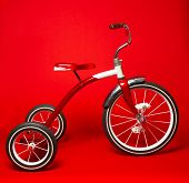 A vintage red tricycle on a bright red background