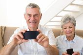 Senior couple sitting on couch using their smartphones at home in living room