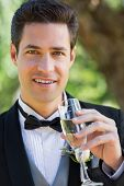Closeup portrait of handsome groom drinking champagne in garden