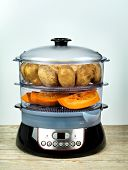 Healthy food in steamer, steam cooker with potato and pumpkin