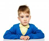 Unhappy little boy in blue cardigan and yellow shirt
