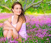 Portrait of beautiful calm girl sitting down on pink floral glade under blooming apple tree, relaxation outdoors in spring time