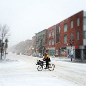 Montreal, Quebec, Canada - March 12, 2014: Cyclist Is Riding In The Snow During Unexpected Snowstorm