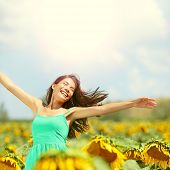 Happy woman in sunflower field. Summer girl in flower field cheerful and joyful. Multiracial Asian C