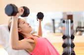 stock photo of shoulders  - Gym woman strength training lifting dumbbell weights in shoulder press exercise - JPG