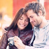 Couple looking at pictures on camera. Beautiful young lovers having fun together outside looking at