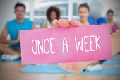 Woman holding pink card saying once a week against yoga class in gym