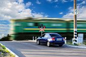 picture of railroad car  - Rail crossing with a moving train and waiting car - JPG