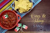 image of dipping  - Happy Cinco de Mayo 5th May party table celebration with corn chips and salsa dip mexican flags and sample text or copy space for your text.