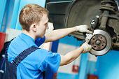 car mechanic replacing car wheel brake shoes of lifted automobile at repair service station