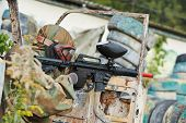 image of paintball  - paintball sport player man in protective camouflage uniform and mask with marker gun outdoors - JPG