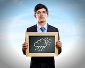 Young businessman holding frame with weather drawings