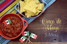 image of mexican fiesta  - Happy Cinco de Mayo 5th May party table celebration with corn chips and salsa dip mexican flags and sample text or copy space for your text. ** Note: Shallow depth of field - JPG
