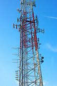 Multiple antennas of transmitting tower against blue sky.