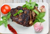 picture of brisket  - Delicious Roasted Brisket of Pork Baked in Herbs Full Body with Basil Garlic and Tomato closeup on Grey Plate - JPG