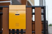 Yellow Mailbox On Brown Fence