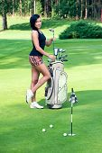 Sexy femail brunette golfer with golf equipment