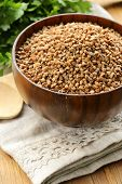 raw buckwheat groats in a wooden bowl on  table