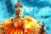 foto of lord krishna  - Brass idol of baby lord Krishna a Hindu god dressed in bright yellow clothing against a polka dotted aqua colored cloth background - JPG
