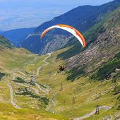 Unidentified paraglider in Balea Lake Fagaras Mountain Romania.