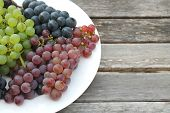 Colorful Grapes On A White Plate On A Rustic Wooden Table