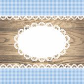 white blank empty lace frame doily and ribbons blue checkered border on a rustic wooden texture