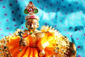 pic of mahabharata  - Brass idol of baby lord Krishna a Hindu god dressed in bright yellow clothing against a polka dotted aqua colored cloth background - JPG