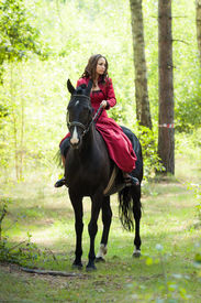 foto of horse girl  - young beautiful brunette girl in red dress ride on the black horse in green forest - JPG