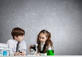 stock photo of experiments  - Two cute children at chemistry lesson making experiments - JPG