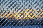 image of chain link fence  - A close up shot of thick layer of ice covering a frozen metal chain link fence after an ice storm - JPG