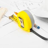 Yellow Measure Tape With Gloves, Construction Helmet And Pencil Above Blueprint