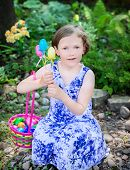 pic of easter basket eggs  - A portrait of a happy young girl sitting outside smiling holding an Easter basket and Easter eggs during an Easter egg hunt - JPG