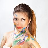 Woman face painted. Beautiful fashion color girl face art close up portrait.